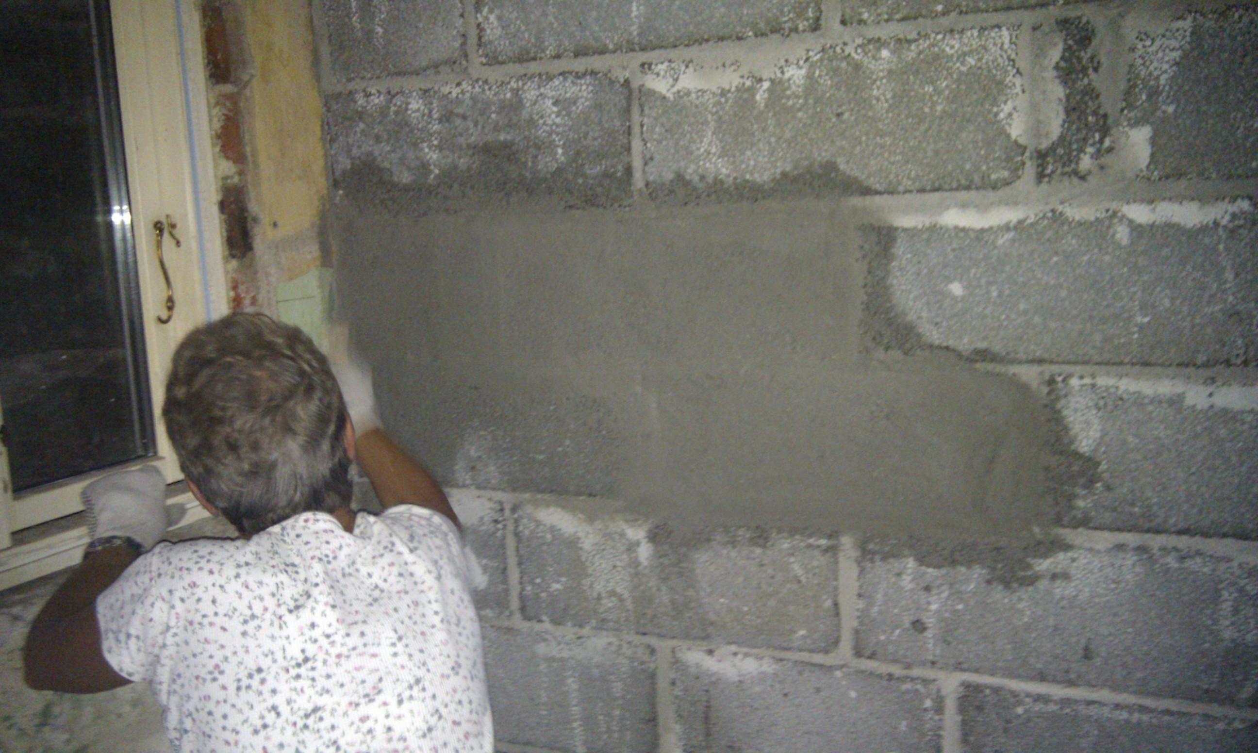 Svigermor er igang med at give leca væggen tynd mørtel lag